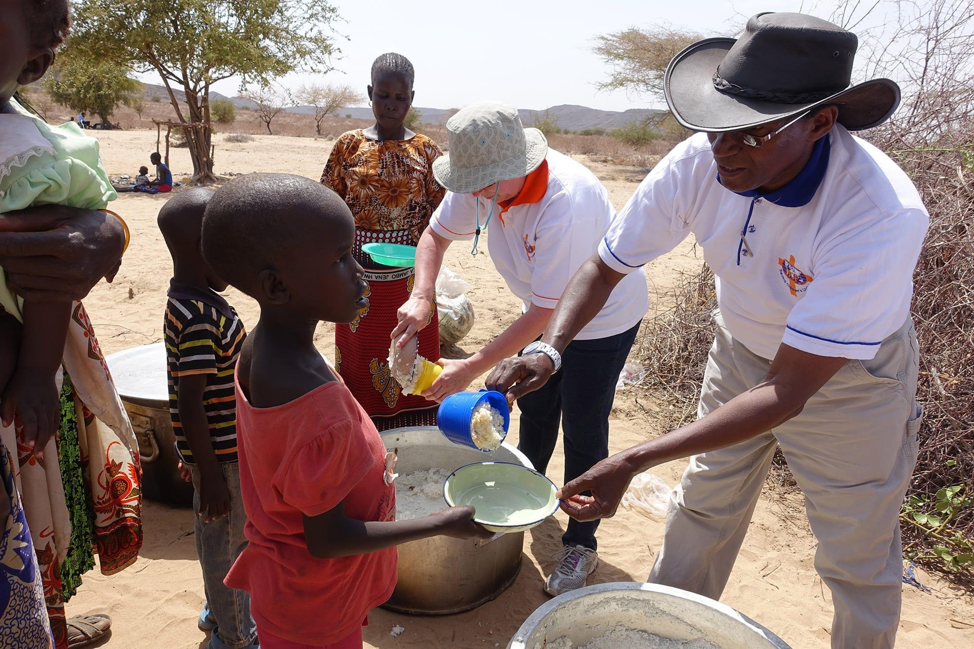 Charles Mulli serving food to children