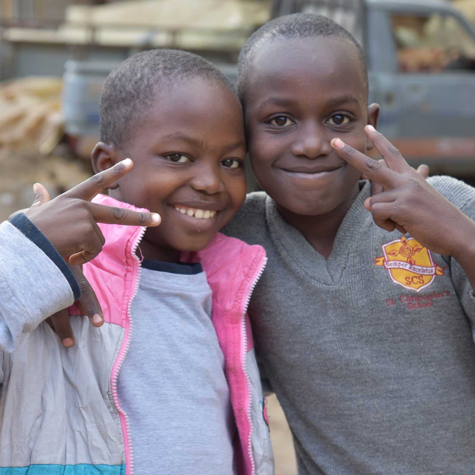 Boys playfully display peace sign