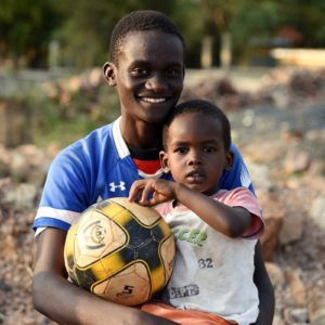 photo: older boy with soceer ball and younger boy