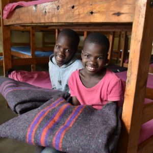 photo: girls sitting with blankets in dormitory